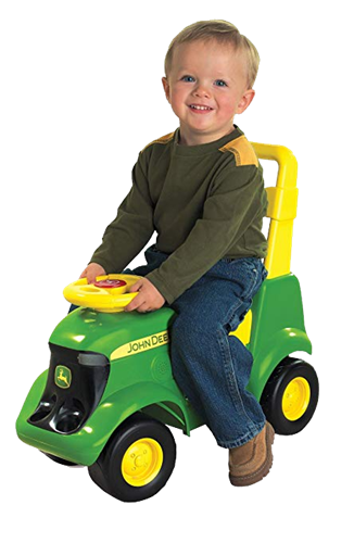 A smiling toddler on a toy green tractor